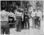 A group of people at an unknown location.  Curley Fletcher is in the middle with the vest on. He...