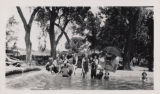 Photograph of a group of people in and around swimming pool at Ladd's Resort, Las Vegas, circa 1910
