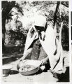 Photograph of an Indian woman displaying the contents of a shallow cooking pan, Manse Ranch,...