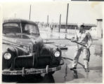Photograph of Sherwin Garside washing a car, Camp Phillips, Kansas, circa 1940s.