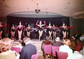 Photograph of the Copa Girls peforming in black costumes with long red gloves and tiaras, Las...