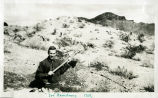Photograph of Irv Armstrong digging a trench in the desert, Eldorado Canyon, Nelson (Nev.), 1907