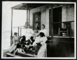 Photograph of women and dogs sitting on porch stairs, Las Vegas (Nev.), 1900-1925
