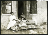 Photograph of women sitting on the porch steps with cats and dogs, Las Vegas (Nev.), 1900-1925