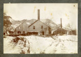 Photograph of abandoned mill buildings with snow, Delamar (Nev.), 1900-1925