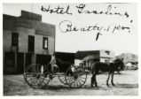Photograph of man driving wagon in front of hotel, Beatty (Nev.), early 1900s