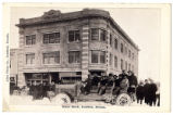Postcard of people and automobiles in front of the Nixon Block Building, Goldfield (Nev.),...