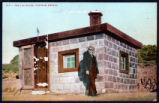 Postcard of a man standing in front of house made of metal cans, Tonopah, (Nev.), 19000-1920