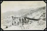 Photograph of men standing near hillside pipeline, Round Mountain (Nev.), early 1900s