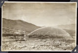 Photograph of water spraying from pipeline in Round Mountain (Nev.), early 1900s